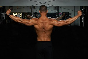Mid adult man, lifting weights, rear view